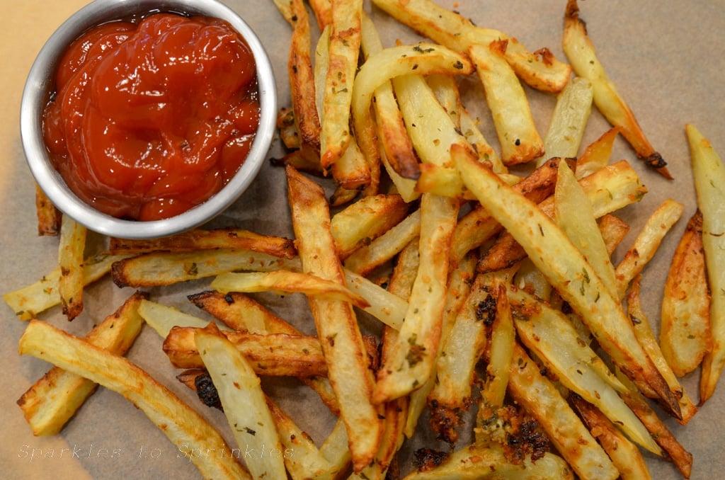 ninja foodi grill garlic fries sitting next to a small bowl of ketchup